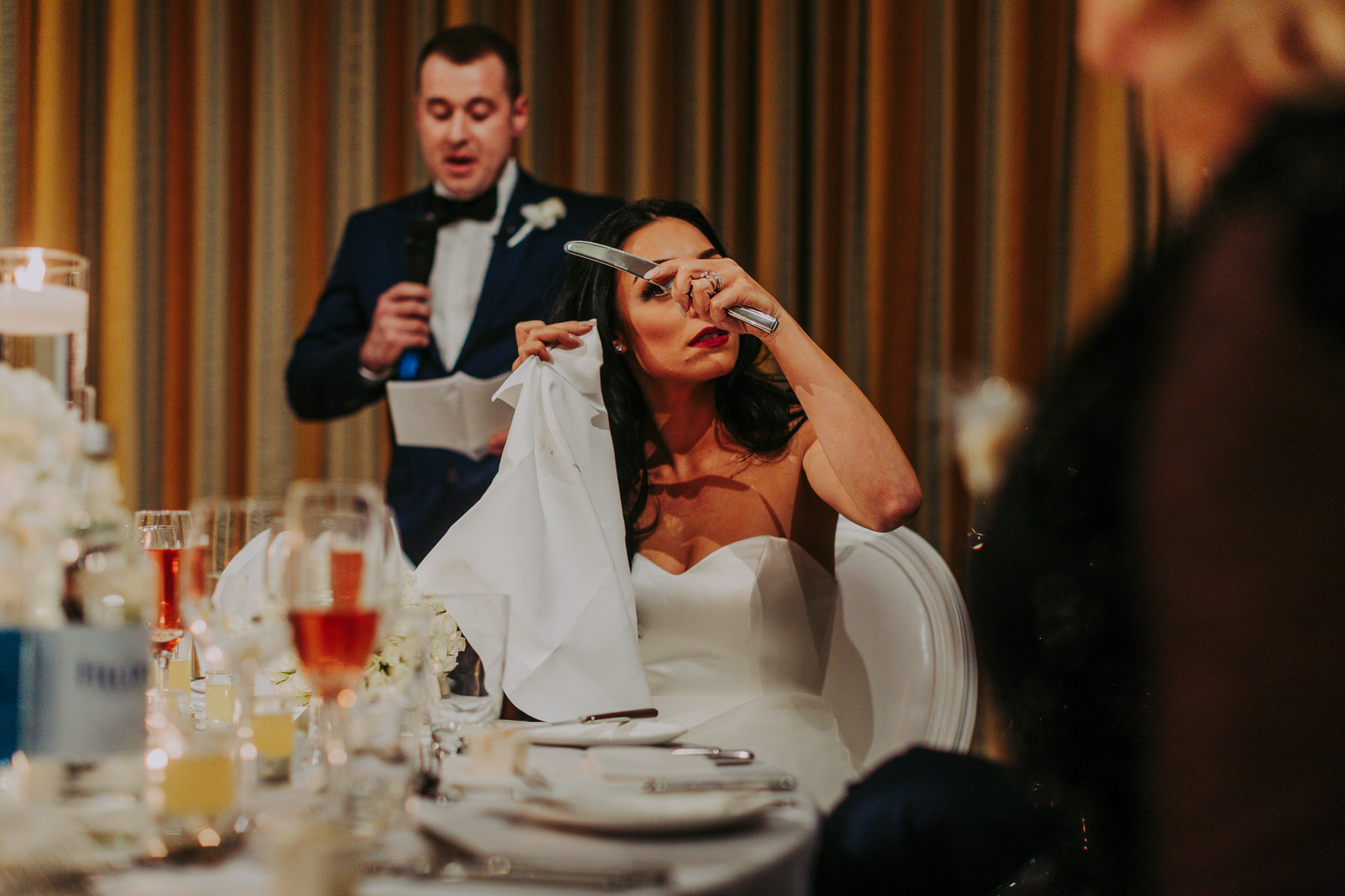 bride looking into knife at speeches at Rudding Park Wedding