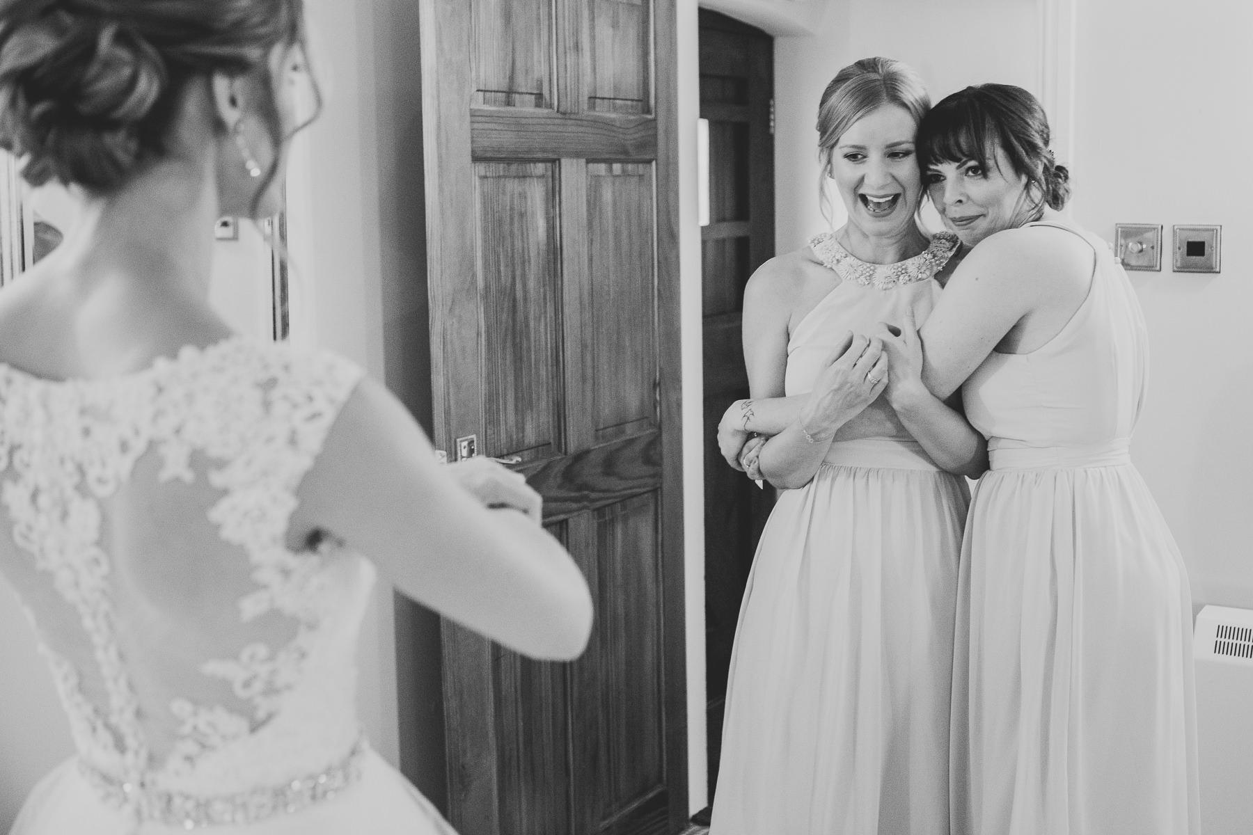 bridesmaid looking at bride Sandhole Oak Barn Wedding