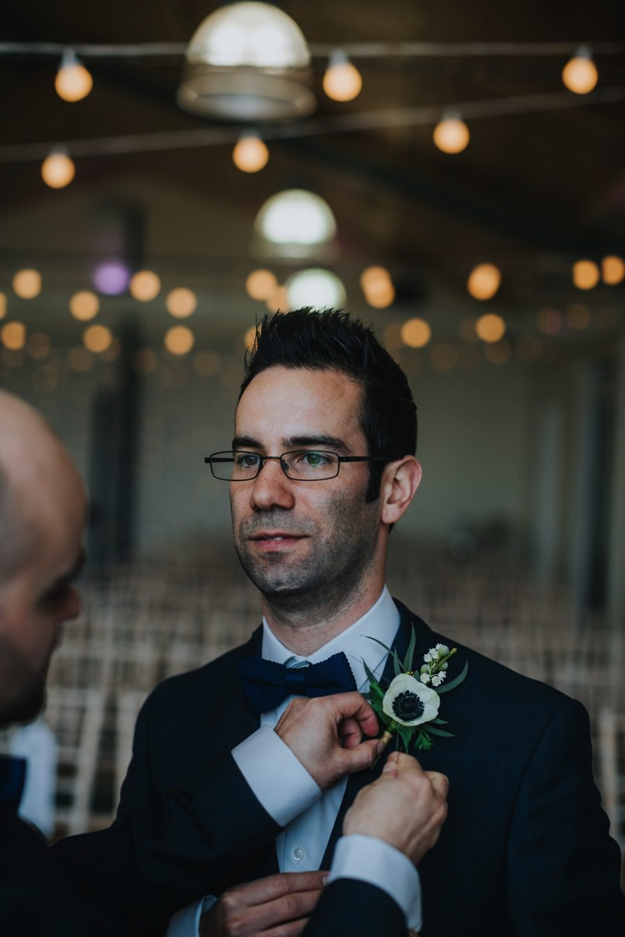 groom putting on button hole at natural retreats wedding