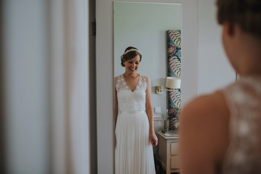 bride looking at herself at the devonshire fell wedding